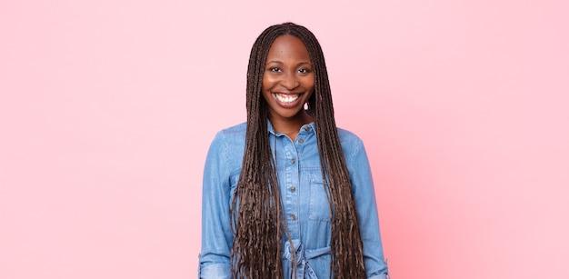 Afro czarna dorosła kobieta uśmiechająca się radośnie i od niechcenia z pozytywnym, szczęśliwym, pewnym siebie i zrelaksowanym wyrazem