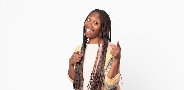Afro czarna dorosła kobieta uśmiechająca się z pozytywnym, odnoszącym sukcesy, szczęśliwym nastawieniem wskazująca na kamerę, robiąca znak pistoletu rękami