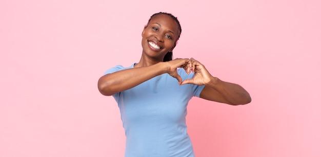 Afro czarna dorosła kobieta uśmiechnięta i czująca się szczęśliwa, urocza, romantyczna i zakochana, tworząca kształt serca obiema rękami