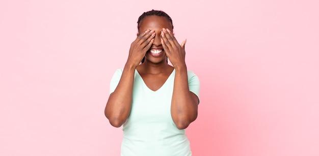Afro czarna dorosła kobieta uśmiechnięta i szczęśliwa, zakrywająca oczy obiema rękami i czekająca na niewiarygodną niespodziankę