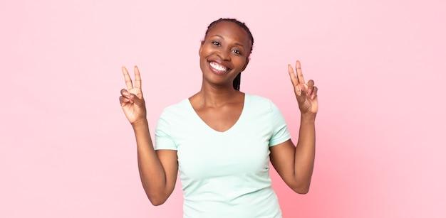Afro czarna dorosła kobieta uśmiechnięta i wyglądająca na szczęśliwą, przyjazną i zadowoloną, gestykulującą zwycięstwo lub pokój obiema rękami