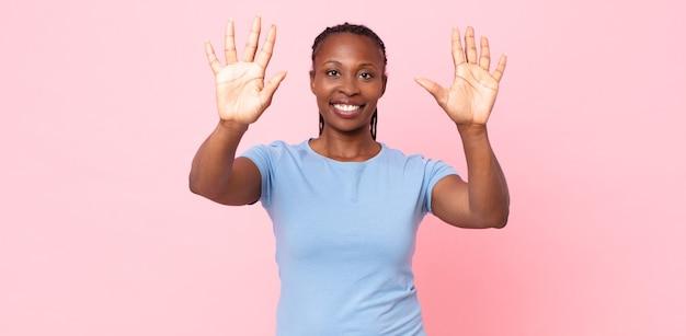 Afro czarna dorosła kobieta uśmiechnięta i wyglądająca przyjaźnie, pokazująca liczbę dziesięć lub dziesiątą z ręką do przodu, odliczając w dół