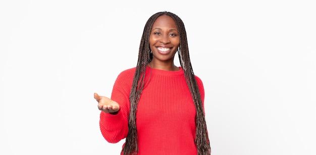 Afro czarna dorosła kobieta uśmiechnięta, wyglądająca na szczęśliwą, pewną siebie i przyjazną, oferująca uścisk dłoni, aby zamknąć transakcję, współpracująca