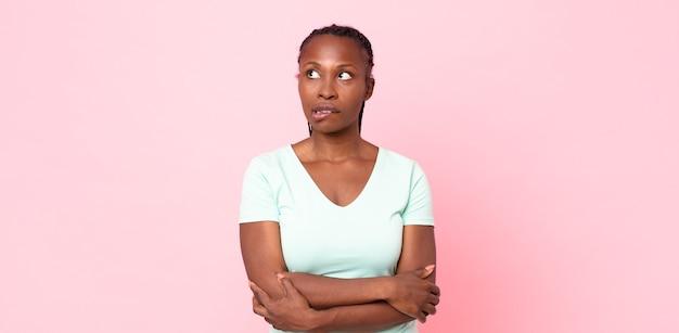 Afro czarna dorosła kobieta wątpi lub myśli, przygryza wargę i czuje się niepewnie i nerwowo, chcąc skopiować przestrzeń z boku