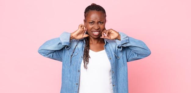 Afro czarna dorosła kobieta wyglądająca na rozgniewaną, zestresowaną i zirytowaną, zakrywającą obydwoje uszy ogłuszającym hałasem, dźwiękiem lub głośną muzyką