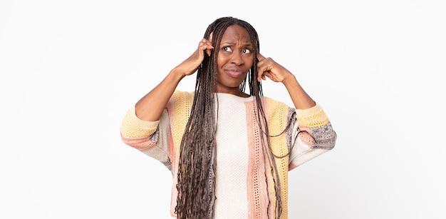 Afro czarna dorosła kobieta wyglądająca na skoncentrowaną i intensywnie myślącą o pomyśle, wyobrażającą sobie rozwiązanie wyzwania lub problemu