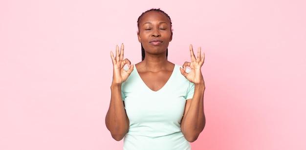 Afro czarna dorosła kobieta wyglądająca na skoncentrowaną i medytującą, czującą się usatysfakcjonowana i zrelaksowana, myśląca lub dokonująca wyboru