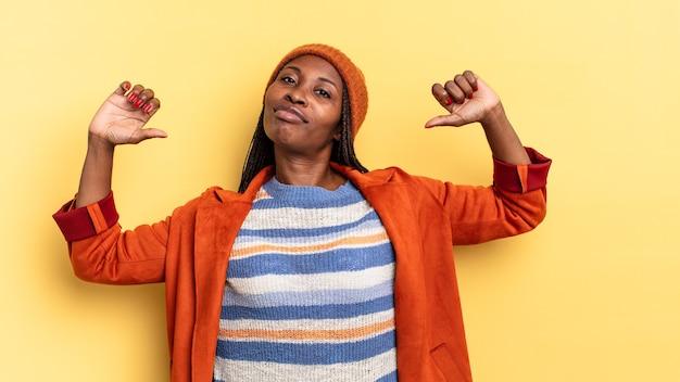 Afro czarna ładna kobieta czuje się dumna, arogancka i pewna siebie, wygląda na zadowoloną i odnoszącą sukcesy, wskazując na siebie
