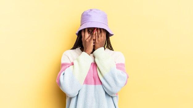 Afro czarna ładna kobieta czuje się przestraszona lub zawstydzona, zerka lub podgląda z oczami na wpół zakrytymi rękami