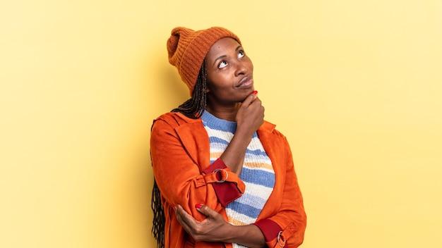 Afro czarna ładna kobieta czuje się zamyślona, zastanawia się lub ma pomysły, marzy i patrzy w górę, aby skopiować przestrzeń