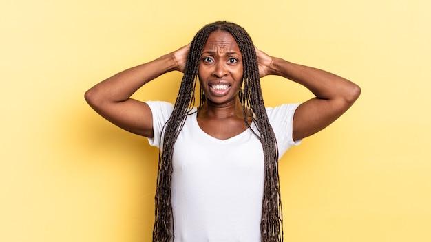Afro czarna ładna kobieta czuje się zestresowana, zmartwiona, niespokojna lub przestraszona, z rękami na głowie, panikując z powodu błędu