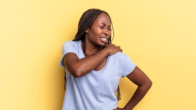 Afro czarna ładna kobieta czuje się zmęczona, zestresowana, niespokojna, sfrustrowana i przygnębiona, cierpi z powodu bólu pleców lub szyi