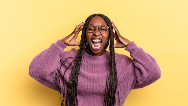 Afro czarna ładna kobieta krzycząca w panice lub złości, zszokowana, przerażona lub wściekła, z rękami przy głowie