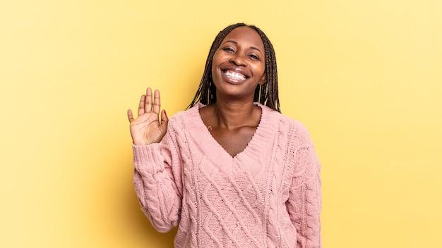 Afro czarna ładna kobieta uśmiecha się radośnie i radośnie, macha ręką, witając cię i pozdrawiając lub żegnając się