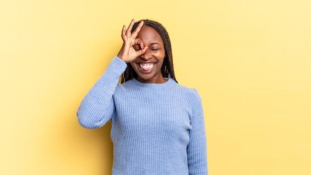 Afro czarna ładna kobieta uśmiecha się radośnie z zabawną miną, żartuje i patrzy przez wizjer, szpiegując sekrety