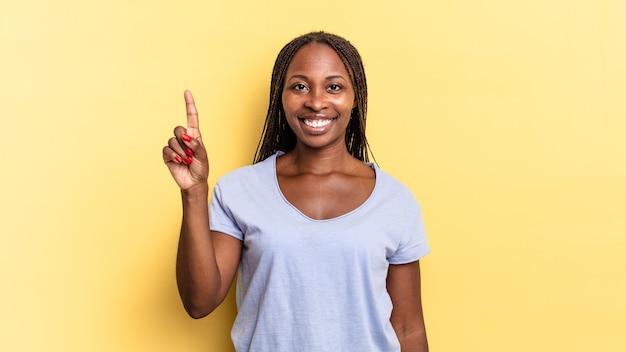 Afro czarna ładna kobieta uśmiechnięta i wyglądająca przyjaźnie, pokazująca numer jeden lub pierwsza z ręką do przodu, odliczając w dół