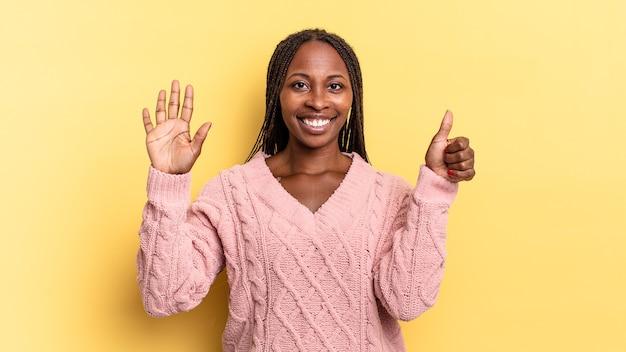 Afro czarna ładna kobieta uśmiechnięta i wyglądająca przyjaźnie, pokazująca numer sześć lub szósty z ręką do przodu, odliczając w dół