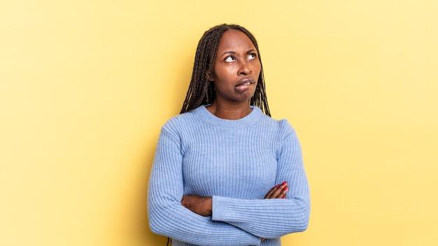 Afro czarna ładna kobieta wątpi lub myśli, przygryza wargę i czuje się niepewnie i zdenerwowana, chcąc skopiować przestrzeń z boku