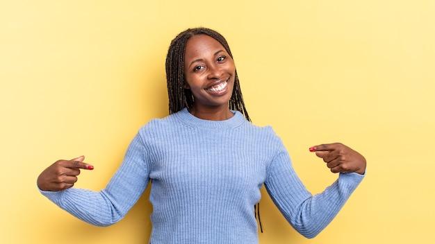 Afro czarna ładna kobieta wyglądająca na dumną, arogancką, szczęśliwą, zaskoczoną i zadowoloną, wskazującą na siebie, czującą się jak zwycięzca