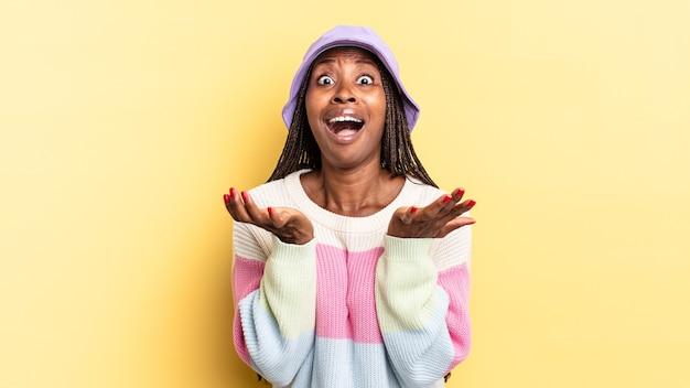 Afro czarna ładna kobieta wyglądająca na zdesperowaną i sfrustrowaną, zestresowaną, nieszczęśliwą i zirytowaną, krzyczącą i krzyczącą