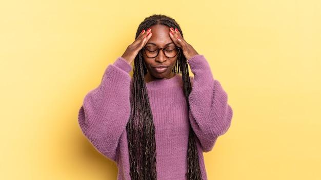 Afro czarna ładna kobieta wyglądająca na zestresowaną i sfrustrowaną, pracująca pod presją, z bólem głowy i z problemami