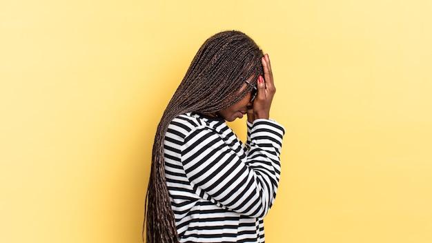 Afro czarna ładna kobieta zakrywająca oczy dłońmi ze smutnym, sfrustrowanym wyrazem rozpaczy, płaczu, widoku z boku