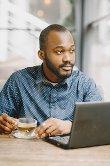 Afro-człowiek pracujący za laptopem. mężczyzna z brodą siedzi w kawiarni i pije herbatę.