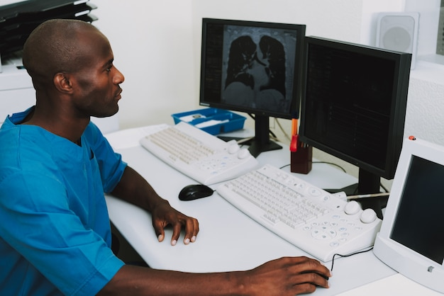 Afro doctor examining scan of lungs ct diagnostic.