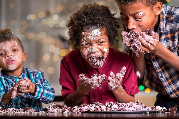 Afro dzieci łapczywie jedzą ciasto. trzech chłopców pożera małe ciastko. witamy na naszej skromnej imprezie. wspólne świętowanie to świetna zabawa.