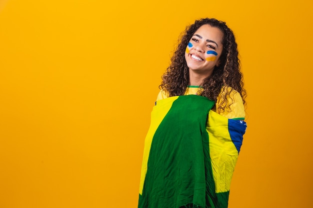 Afro dziewczyna kibicująca ulubionej brazylijskiej drużynie, trzymająca flagę narodową na żółtym tle.