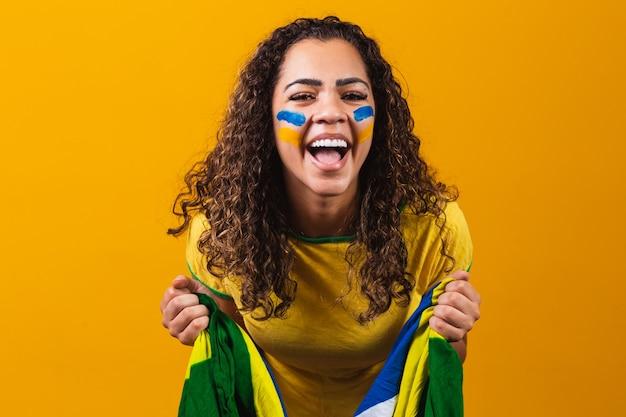 Afro dziewczyna kibicuje ulubionej brazylijskiej drużynie, trzymając flagę narodową na żółtym tle.