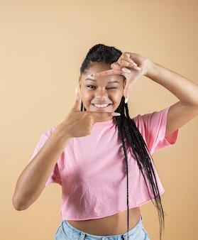Afro dziewczyna robi gest fotograficzny w studio