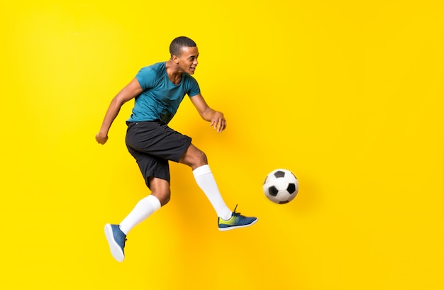 Afro futbolu amerykańskiego gracza mężczyzna nad odosobnionym kolorem żółtym