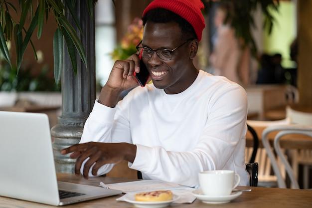 Afro hipster mężczyzna nosić czerwony kapelusz rozmawia na zdalny telefon komórkowy online, pracując na komputerze przenośnym w kawiarni