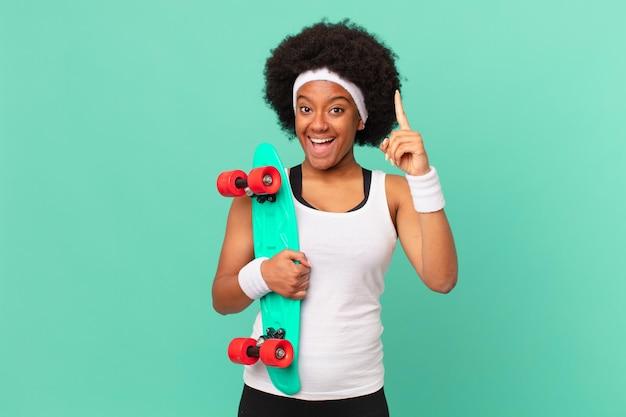 Afro kobieta czując się jak szczęśliwy i podekscytowany geniusz po zrealizowaniu pomysłu, radośnie podnosząc palec, eureka!. koncepcja deskorolki