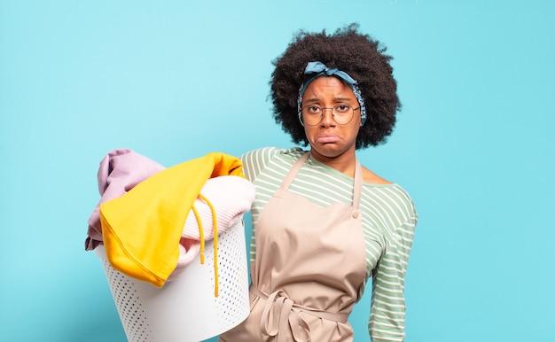 Afro kobieta czuje się smutna i marudna z nieszczęśliwym spojrzeniem, płacze z negatywnym i sfrustrowanym nastawieniem. koncepcja sprzątania.
