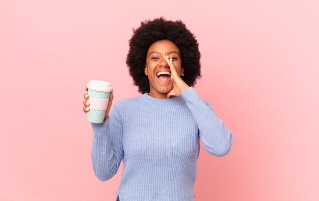 Afro kobieta czuje się szczęśliwa, podekscytowana i pozytywna, wydając wielki okrzyk z rękami przy ustach, wołając. koncepcja kawy