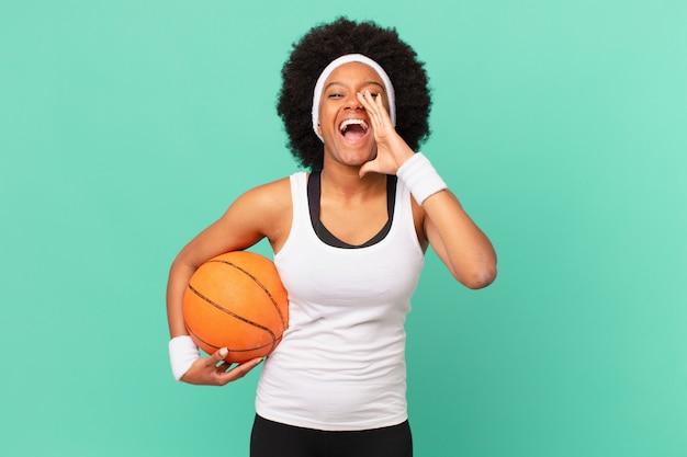 Afro kobieta czuje się szczęśliwa, podekscytowana i pozytywna, wydając wielki okrzyk z rękami przy ustach, wołając. koncepcja koszykówki