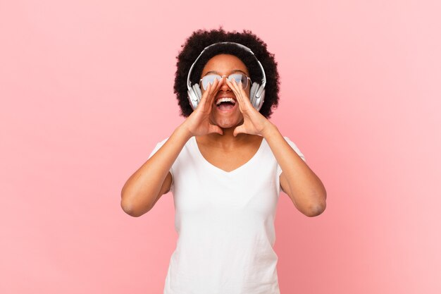 Afro kobieta czuje się szczęśliwa, podekscytowana i pozytywna, wydając wielki okrzyk z rękami przy ustach, wołając. koncepcja muzyki