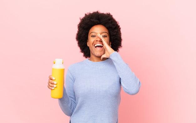Afro kobieta czuje się szczęśliwa, podekscytowana i pozytywna, wydając wielki okrzyk z rękami przy ustach, wołając. koncepcja smoothie