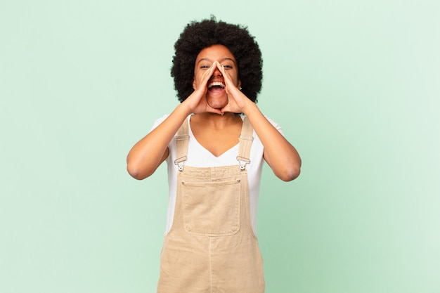 Afro kobieta czuje się szczęśliwa, podekscytowana i pozytywna, wydając wielki okrzyk z rękami przy ustach, wykrzykując koncepcję szefa kuchni