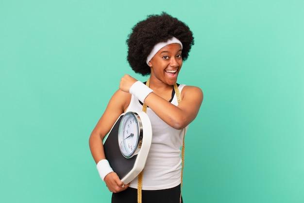 Afro kobieta czuje się szczęśliwa, pozytywna i odnosząca sukcesy, zmotywowana, gdy staje przed wyzwaniem lub celebruje koncepcję diety dobrych wyników