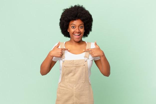 Afro kobieta czuje się szczęśliwa, zaskoczona i dumna, wskazując na siebie z podekscytowaną, zdumioną koncepcją szefa kuchni
