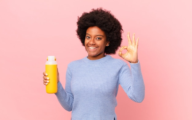 Afro kobieta czuje się szczęśliwa, zrelaksowana i usatysfakcjonowana, okazując aprobatę dobrym gestem, uśmiechając się. koncepcja smoothie