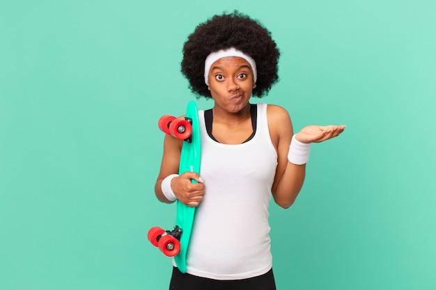 Afro kobieta czuje się zakłopotana i zdezorientowana, wątpi, waży lub wybiera różne opcje z zabawnym wyrazem twarzy. koncepcja deskorolki