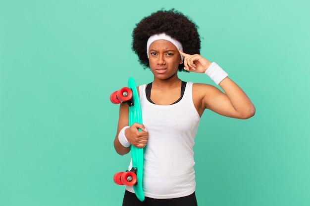 Afro kobieta czuje się zdezorientowana i zakłopotana, pokazując, że jesteś szalony, szalony lub oszalały. koncepcja deskorolki