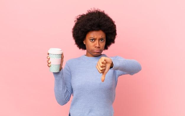 Afro kobieta czuje się zła, zła, zirytowana, rozczarowana lub niezadowolona, pokazując kciuk w dół z poważnym spojrzeniem. koncepcja kawy