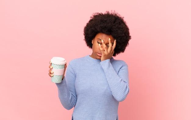 Afro kobieta czuje się znudzona, sfrustrowana i senna po męczącym, nudnym i żmudnym zadaniu, trzymając twarz dłonią. koncepcja kawy