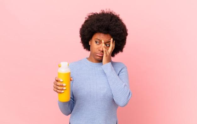 Afro kobieta czuje się znudzona, sfrustrowana i senna po męczącym, nudnym i żmudnym zadaniu, trzymając twarz dłonią. koncepcja smoothie