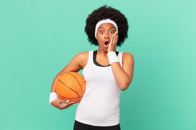 Afro kobieta czuje się zszokowana i przestraszona, wygląda na przerażoną z otwartymi ustami i dłońmi na policzkach. koncepcja koszykówki